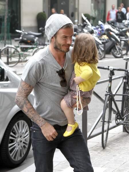 Dans les bras de son papa David Beckham, l'adorable Harper est top tendance (comme maman) en robe Vichy