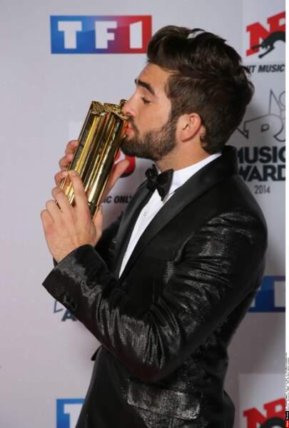 Kendji embrasse l'un des deux trophées qu'il a remporté lors de cette soirée des NRJ Music Awards
