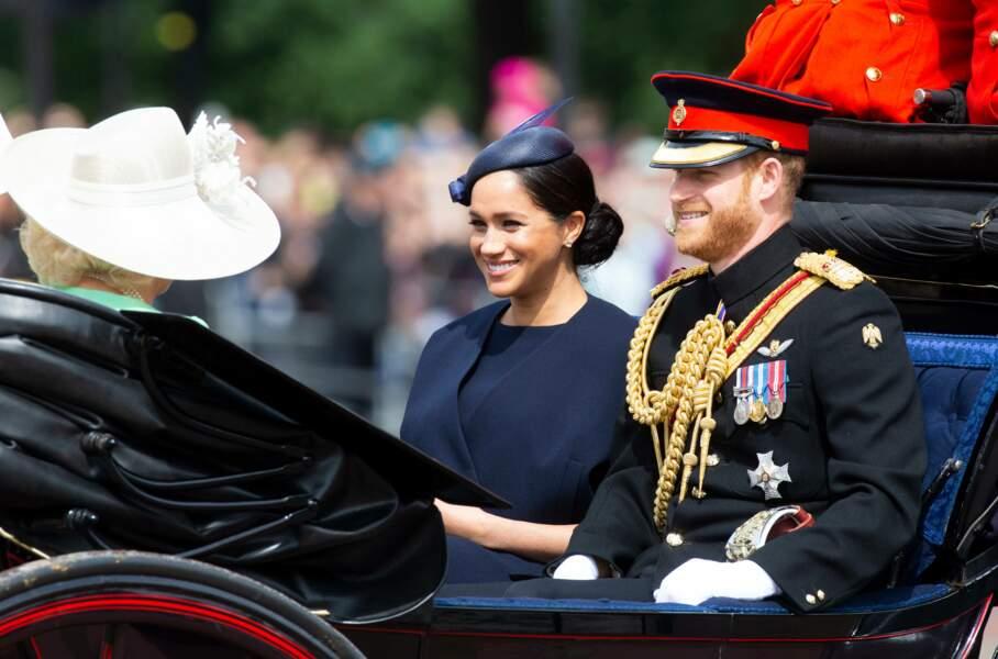 Le prince Harry souriant aux côtés de Meghan Markle