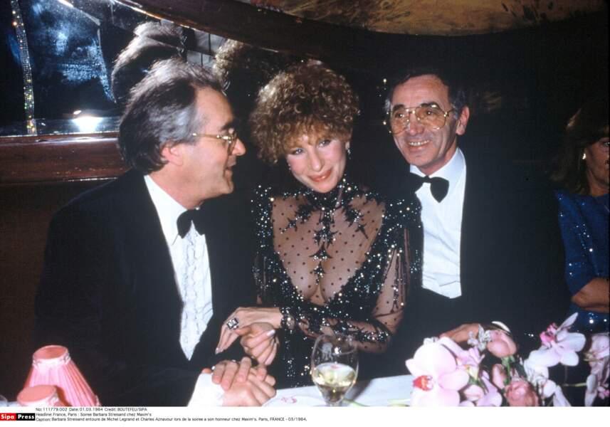 Barbra Streisand avec Michel Legrand et Charles Aznavour lors d'une soirée en son honneur chez Maxim's en 1984