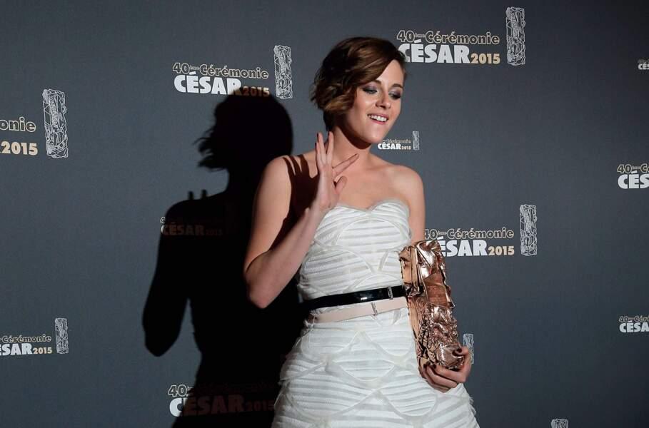 Kristen Stewart (avec son trophée) souriante lors du photocall des César 2015