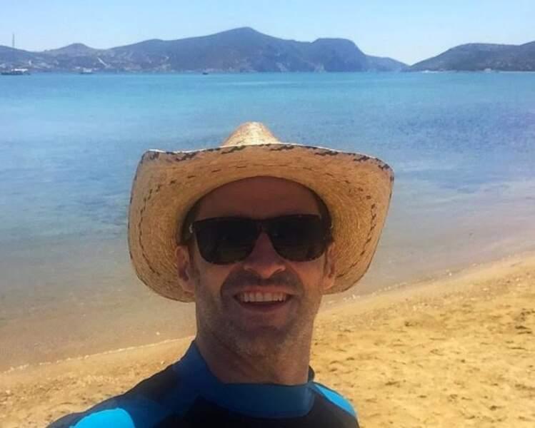 Holà ! Hugh Jackman se promène sur la plage les pieds dans le sable, petit chapeau de paille sur la tête