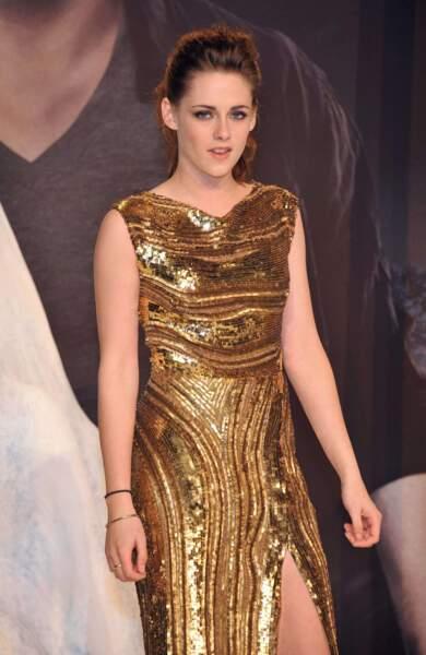 Ah voilà, elle est élégante dans sa jolie robe dorée fendue...