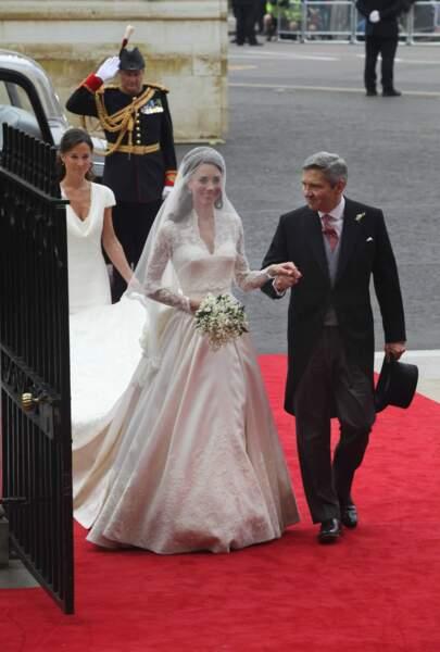 Dans sa robe Alexander McQueen (qui fait aujourd'hui l'objet d'un procès pour plagiat), Kate s'avance avec son père