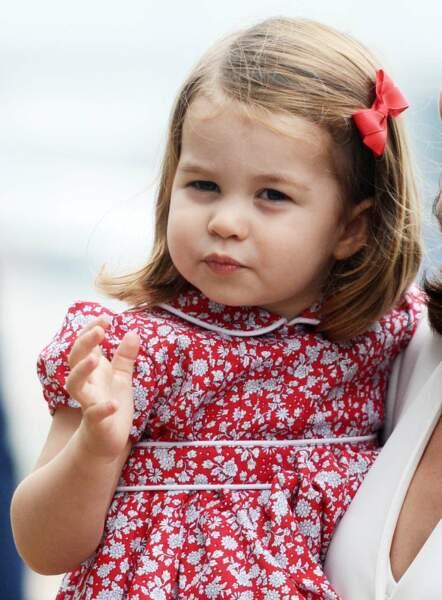 Charlotte porte une ravissante robe rouge fleurie... avec noeud assorti dans les cheveux s'il vous plaît !