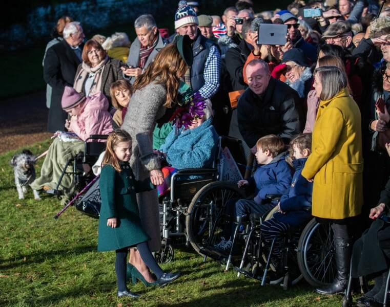 A la sortie de la messe de Noël donnée à l'église Ste Marie-Madeleine de Sandringham, Kate initie sa fille aux bains de foule