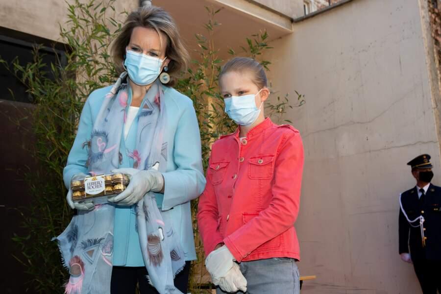 La reine Mathilde et la princesse Eleonore de Belgique masquées pour visiter un restaurant pour sans-abris