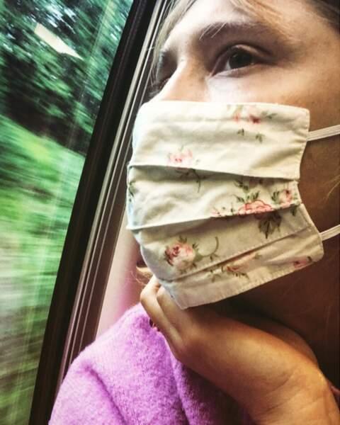 Bérengère Krief, pensive dans le train derrière son joli masque à fleurs