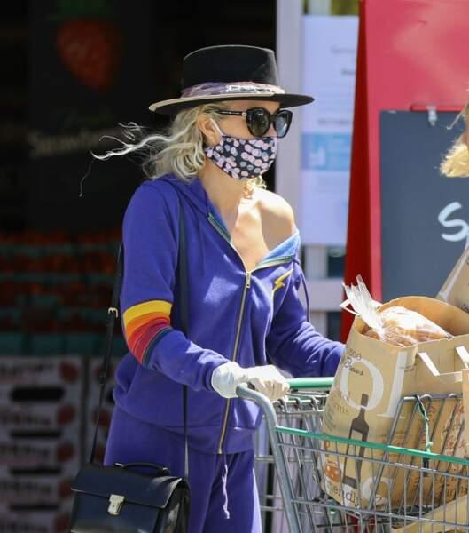Visage masqué, mains gantées et épaule découverte pour Laeticia Hallyday au supermarché