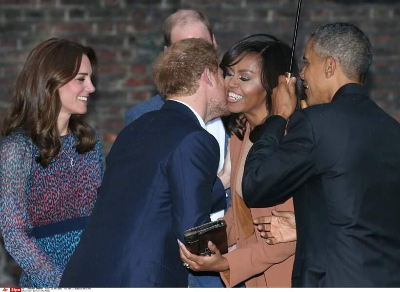 …le prince Harry a planté un baiser sur la joue de Michelle Obama, tandis que le président tenait le parapluie