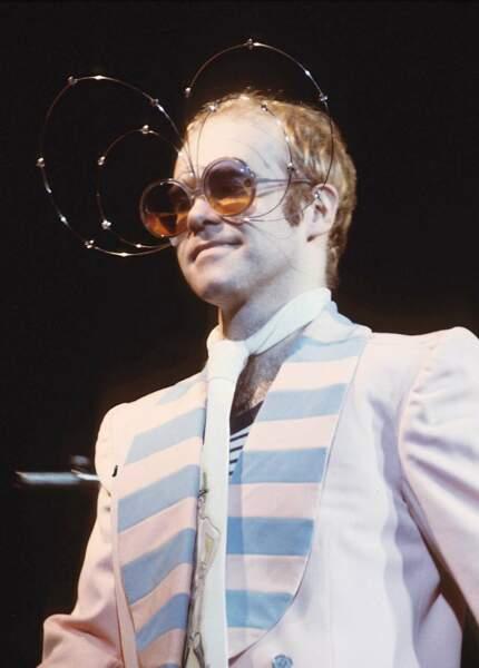 Elton John en concert dans les années 70. Costume plus sobre, mais il se rattrape avec les lunettes