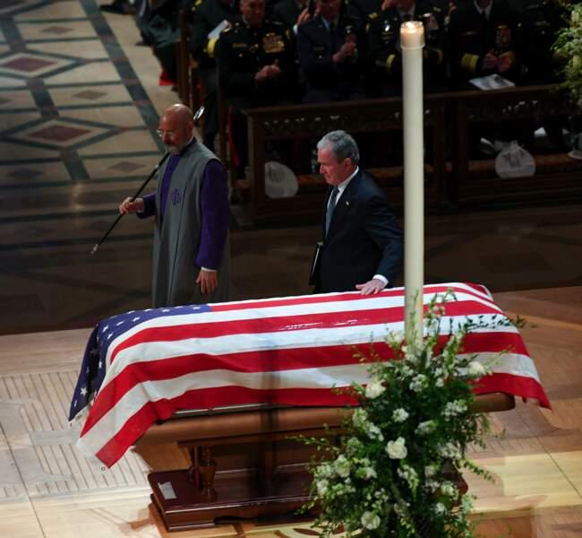 George W. Bush s'incline, la main sur le cercueil de son père
