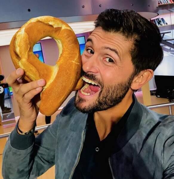 Christophe Beaugrand croque une baguette à la forme du logo Sidaction