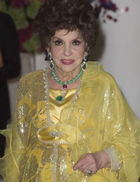 L'actrice italienne Gina Lollobrigida dans une robe jaune pleine de paillettes.