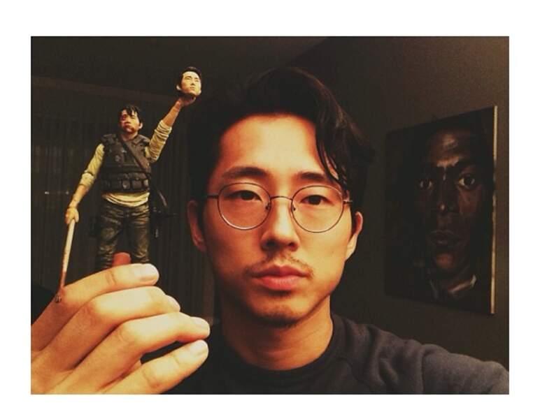 Steven Yeun tenant une figurine de Glenn brandissant la tête de Steven Yeun. Glauque, mais fun !