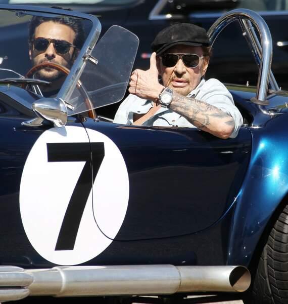 Au volant de sa belle voiture, il tient à montrer qu'il va bien.