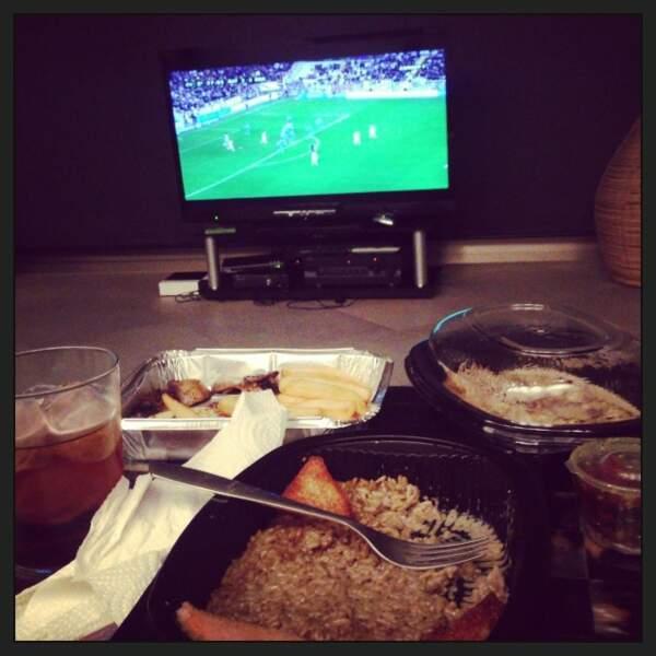 Il se fait des plateaux repas en regardant le football.