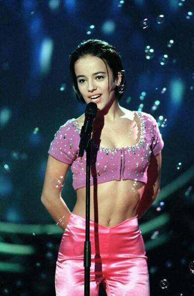 En 2000, Alizée, alors âgée de 16 ans, devient la protégée de Mylène Farmer et enchaîne les tubes.
