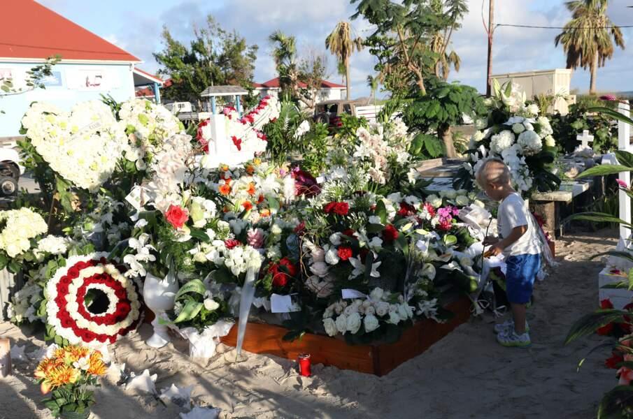 Seulement quelques heures après cette cérémonie, des dizaines de fleurs sont déposées sur la tombe du rockeur