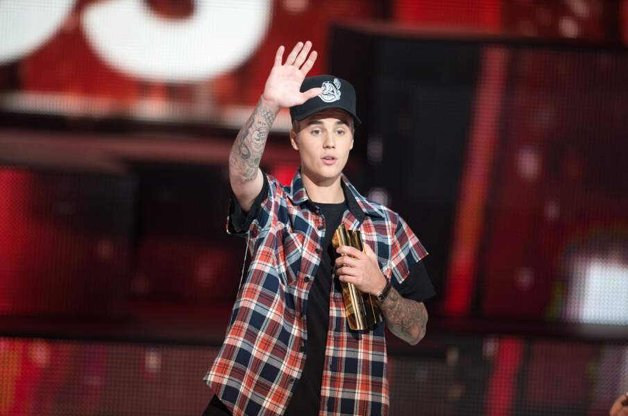 2015, Justin Bieber, casquette et bras tatoués, salue le public
