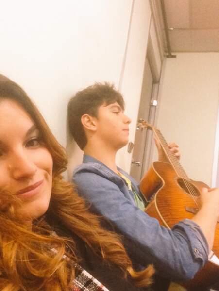Pendant ce temps, dans le couloir, Antoine gratouille sa guitare. Et ça plaît à Gabriella !