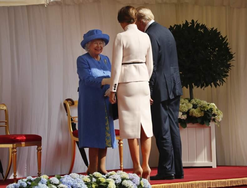 Tout sourire, la reine d'Angleterre serre les mains de ses invités