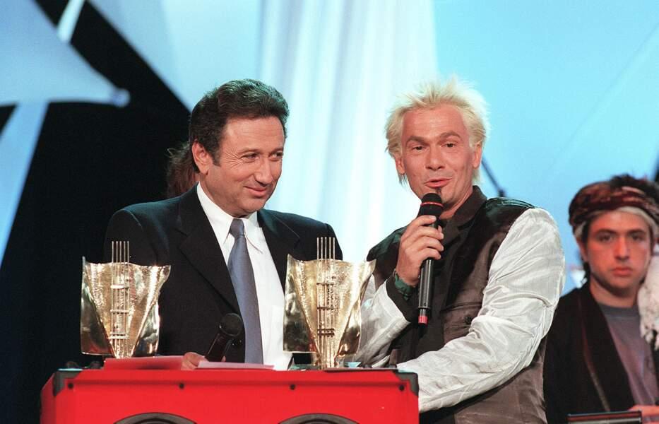 """1998, les cheveux peroxydés, Florent Pagny s'adresse à sa mère par ces mots """"Ça y est maman, on l'a !"""". Récompensé par ses pairs de deux Victoires de la musique, l'une pour meilleur clip et..."""