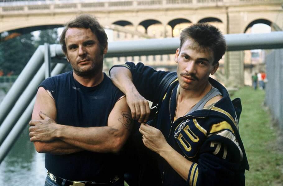 """1983. Cheveux en brosse, petite moustache et boucle d'oreille, Florent donne la réplique à Jean-François Stevenin dans le téléfilm """"L'ennemi public n°2""""."""