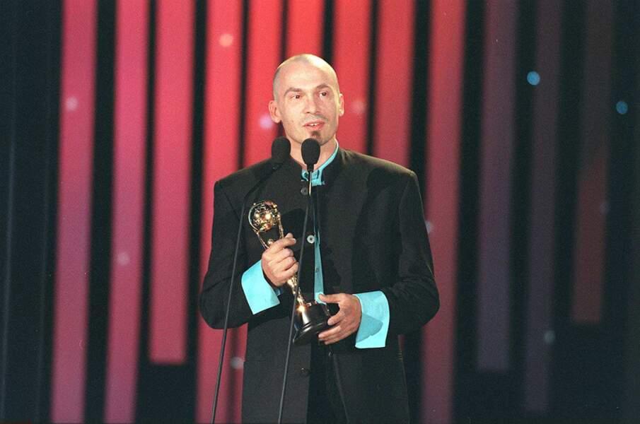 """1997. Lors de World Music Awards, Florent, crâne chauve et petite barbichette, remporte le trophée de l'artiste ayant vendu le plus de disques dans le monde grâce à son album """"Savoir Aimer""""."""