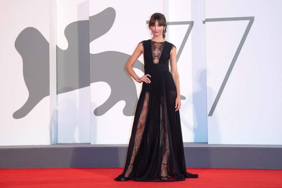 Sa longue robe noire dévoile ses jambes et son décolleté