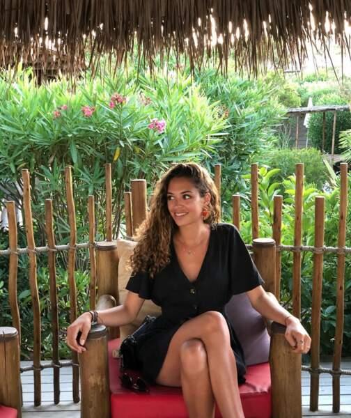 La jeune femme rayonne depuis son trône en bambou