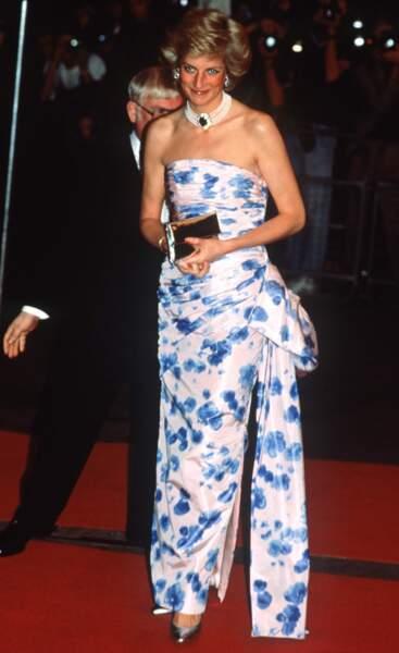 La princesse Diana à Londres lors de l'avant-première d'un film à l'Odeon à Leicester Square élégante dans une robe de soie fleurie dévoilant ses épaules.