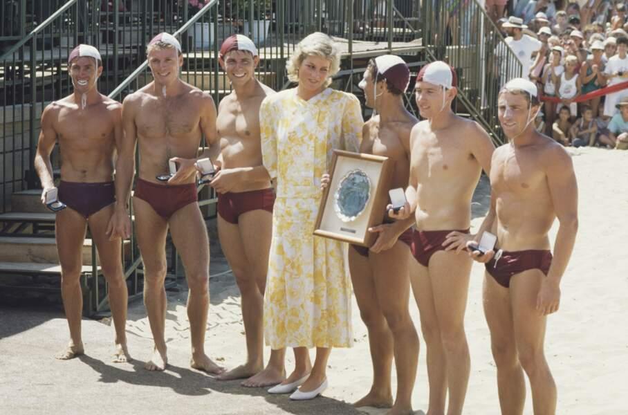 La princesse de Galles pose avec un groupe de sauveteurs au Terrigal Beach Surf Carnival Australie, en janvier 1988. Elle porte une robe jaune et blanche de Paul Costelloe.
