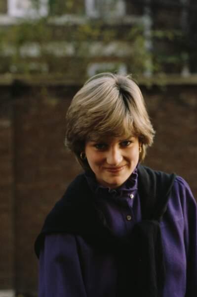 Diana, encore insouciante, sourit malicieusement dans un pull violet.