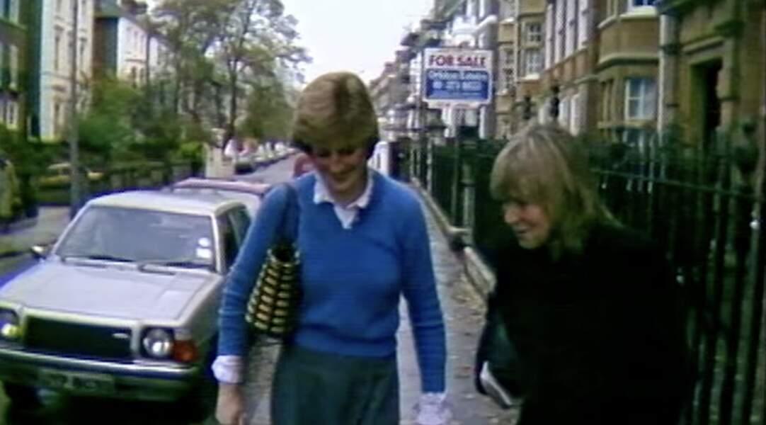 Sous l'œil des caméras depuis qu'elle fréquente officiellement le prince Charles, la jeune Diana porte sa tenue fétiche, un chemisier blanc sous un débardeur bleu.