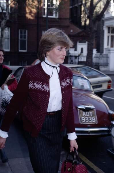 Lady Diana Spencer presse le pas pour éviter les journalistes en sortant de son appartement de Londres à Coleherne Court en 1980. Elle est vêtu d'un chemisier blanc, orné d'un petit nœud, sous un gilet vintage bordeaux aux motifs de Noël.