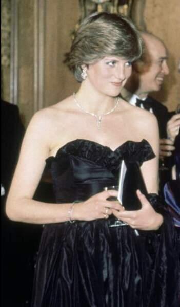 Sans savoior qu'il s'agit d'une entorse à l'étiquette, Lady Diana Spencer jeune fiancée, porte une robe bustier en taffetas de soie noire pour sa première sortie officielle.