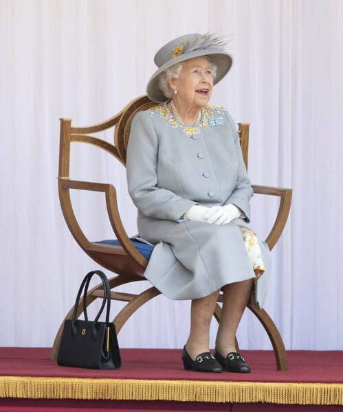 Sous son manteau, la reine portait une robe assortie aux détails brodés sur son col.