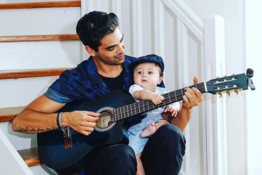 Christophe Licata prend la pose avec son fils et sa guitare.
