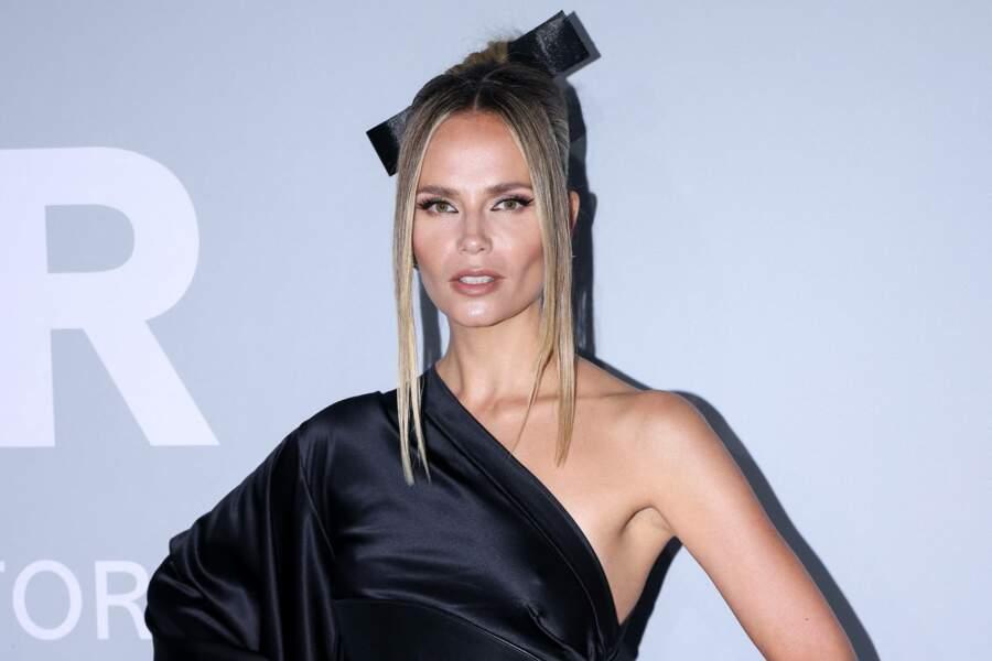Pour parfaire le look, Natasha Poly a lissé ses cheveux blonds et les a orné d'un nœud noire en satin.
