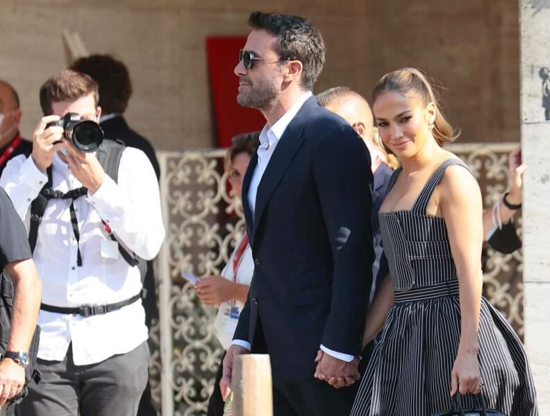 Le couple s'avance main dans la main, dans la ligne de mire des photographes.