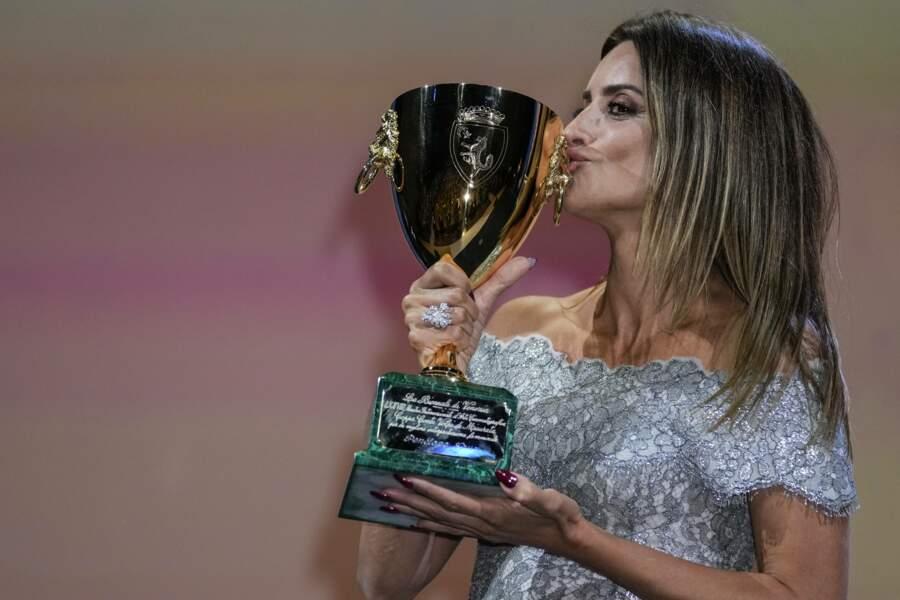 Très contente, elle embrasse même son trophée