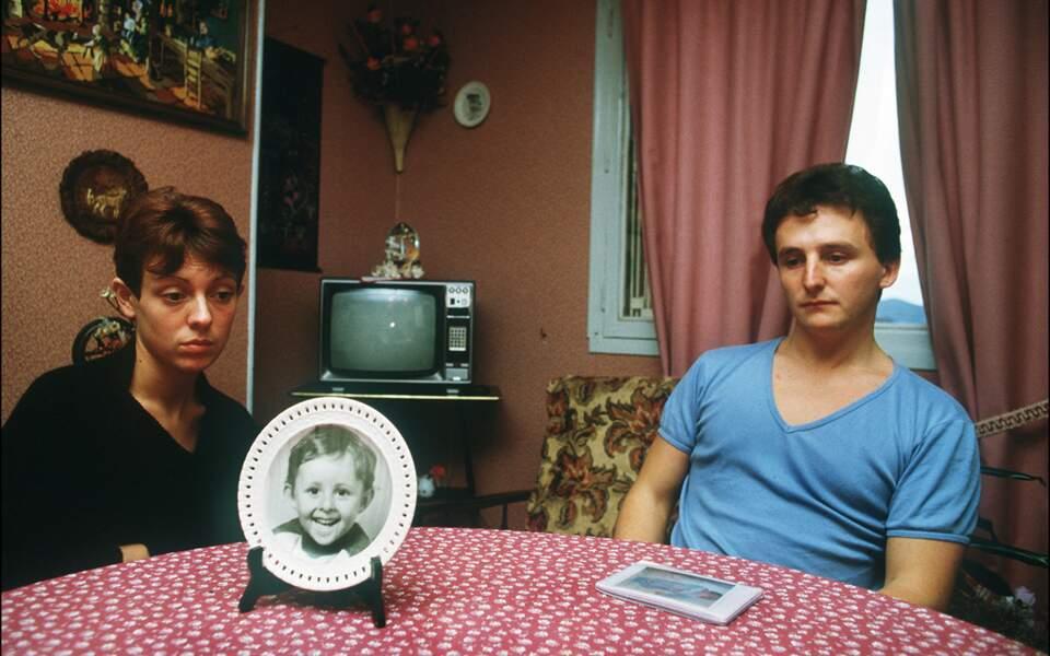 Christine et Jean-Marie Villemin, les parents du petit Grégory, assis autour de la table de leur salle-à-manger sur laquelle est posée une assiette à l'effigie de leur enfant assassiné quelques jours plus tôt.