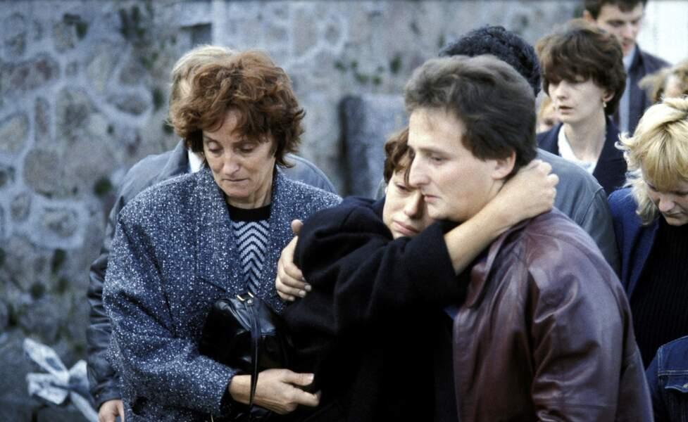 Dévastée dans les bras de son époux Jean-Marie qui la soutient, Christine Villemin s'est évanouie le jour de l'enterrement de son enfant.